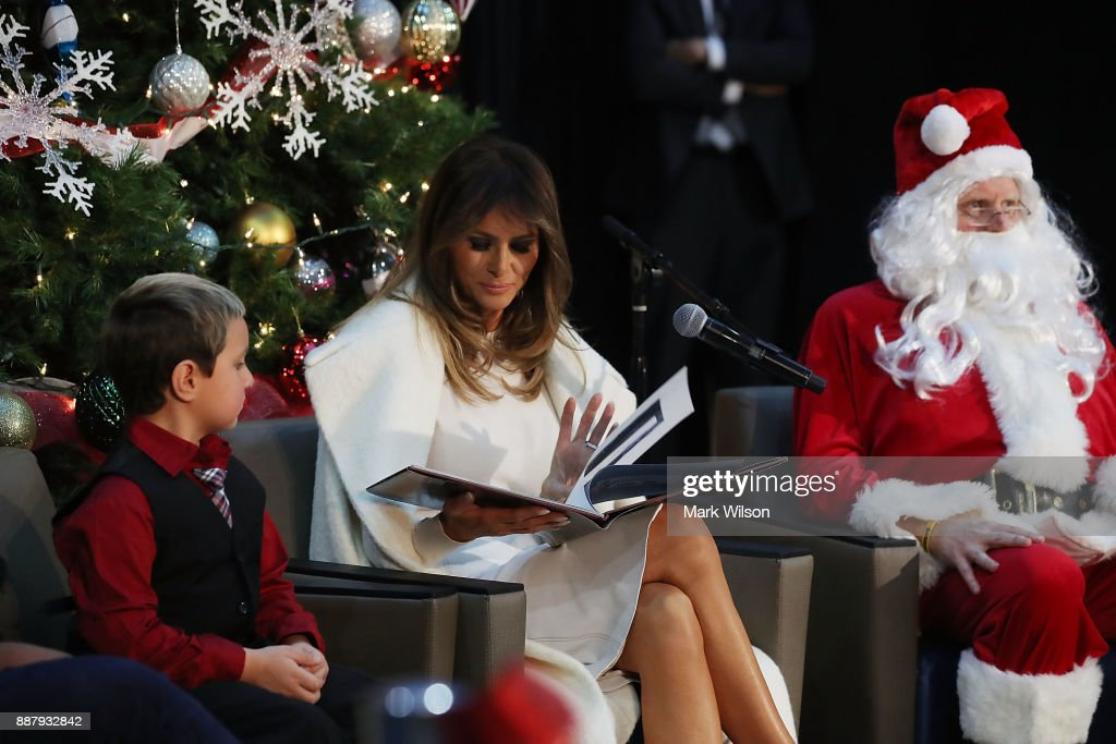 First lady Melania Trump sits between Damian Contreras (L) and a person dressed as Santa Claus as she reads the Christmas book, The Polar Express at Children's National Medical Center, on December 7, 2017 in Washington, DC. First ladies dating back to Jacqueline Kennedy have made the annual visit to the Washington area hospital during the holiday season.