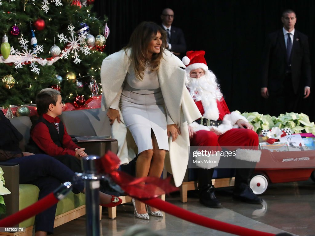 First lady Melania Trump sits Damian Contreras (L) and a person dressed as Santa Claus after reading the Christmas book, The Polar Express to children at Children's National Medical Center, on December 7, 2017 in Washington, DC. First ladies dating back to Jacqueline Kennedy have made the annual visit to the Washington area hospital during the holiday season.
