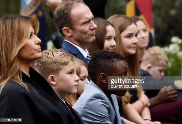 US First Lady Melania Trump sits with the husband of Judge Amy Coney Barrett Jesse Barrett and some of the Barrett children as they gather in the...