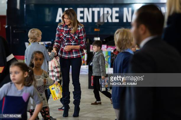US First Lady Melania Trump speaks with a child during a Toys for Tots event at Joint Base AnacostiaBolling in Washington DC on December 11 2018 Toys...