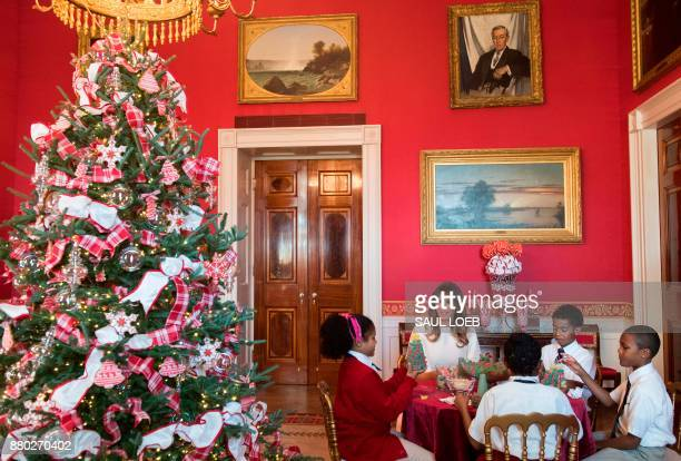 US First Lady Melania Trump speaks with children as they make holiday decorations in the Red Room as she tours Christmas decorations at the White...