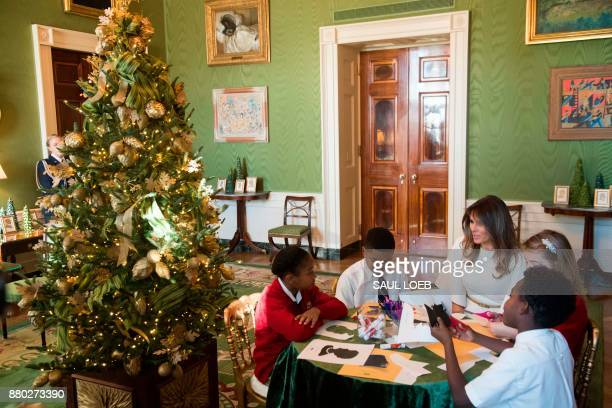 US First Lady Melania Trump speaks with children as they make holiday decorations in the Green Room as she tours Christmas decorations at the White...
