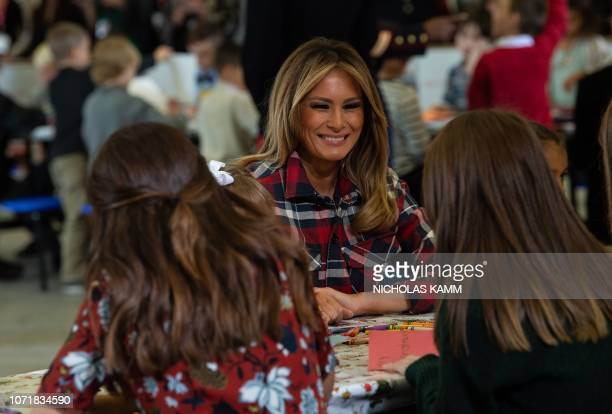 US First Lady Melania Trump speaks with children during a Toys for Tots event at Joint Base AnacostiaBolling in Washington DC on December 11 2018...
