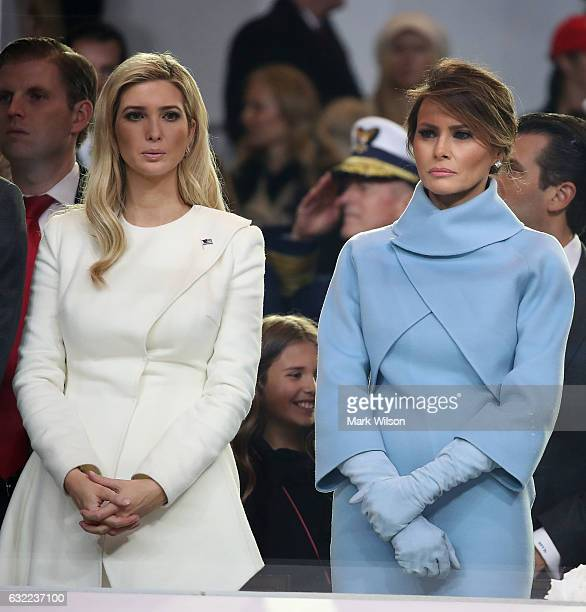 First lady Melania Trump stands with Ivanka Trump as a parade passes the inaugural parade reviewing stand in front of the White House on January 20...
