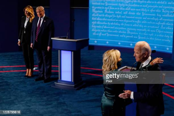 First lady Melania Trump stands with President Donald Trump as he looks at Democratic presidential candidate former Vice President Joe Biden as he is...