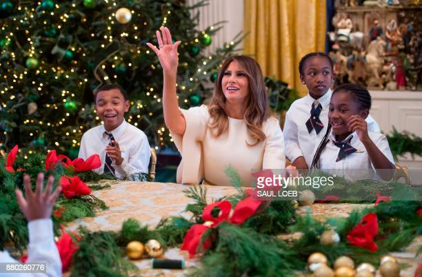 US First Lady Melania Trump throws a Christmas ornament as she makes garland with children in the East Wing as she tours holiday decorations at the...