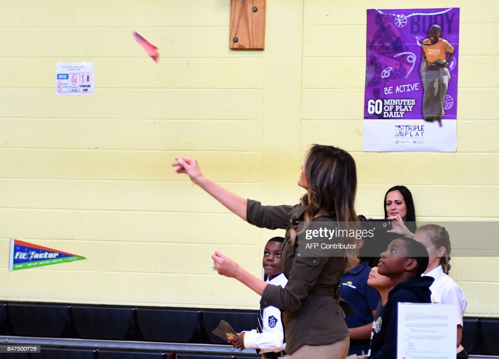 US First Lady Melania Trump throws a paper air plane as students look on as she visits a youth centre at Joint Andrews Airforce base, Maryland on September 15, 2017. /
