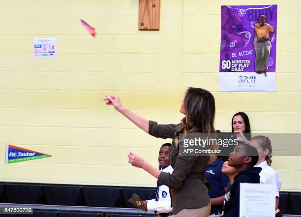 US First Lady Melania Trump throws a paper air plane as students look on as she visits a youth centre at Joint Andrews Airforce base Maryland on...