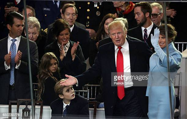 First lady Melania Trump US President Donald Trump and Barron Trump watch the Inaugural Parade from the main reviewing stand in front of the White...