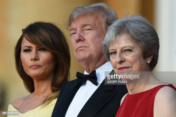 TOPSHOT US First Lady Melania Trump US President Donald Trump and Britain's Prime Minister Theresa May stand on steps in the Great Court as the bands...