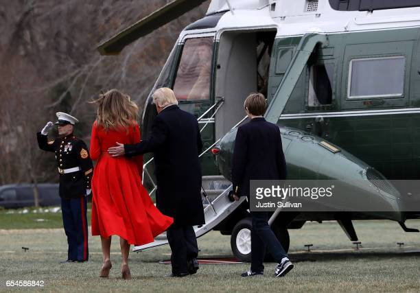 First Lady Melania Trump US President Donald Trump and son Barron Trump prepare to board Marine One as they depart the White House on March 17 2017...