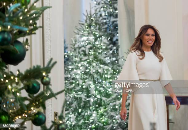US First Lady Melania Trump walks into the East Room as she tours Christmas decorations at the White House in Washington DC November 27 2017 / AFP...