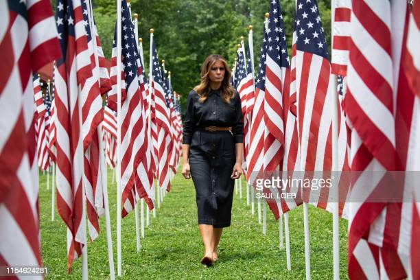 First Lady Melania Trump walks through 453 American flags, each representing a child in foster care in Cabell County, West Virginia, many due to the...