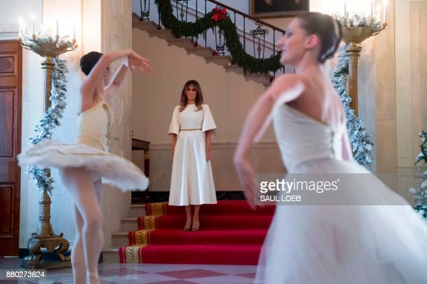 US First Lady Melania Trump watches ballerinas perform in the Grand Foyer as she tours Christmas decorations at the White House in Washington DC...