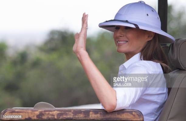 US First Lady Melania Trump waves as she travels in a vehicle while on a safari at The Nairobi National Park in Nairobi on October 5 as she pays a...