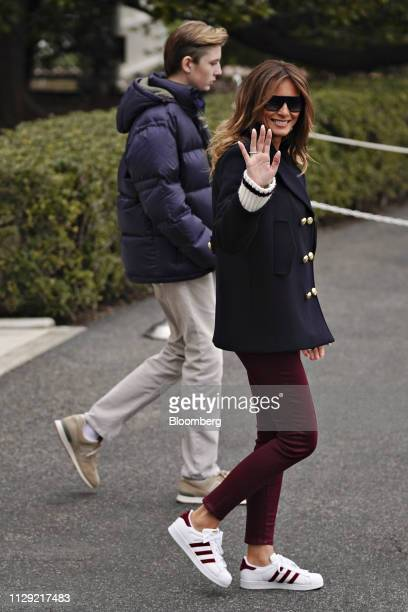 US First Lady Melania Trump waves to members of the media while exiting the White House with son Barron Trump left on the South Lawn of the White...