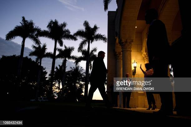 First lady Melania Trump waves to the Florida Atlantic University band after a performance as US President Donald Trump walks into the Trump...