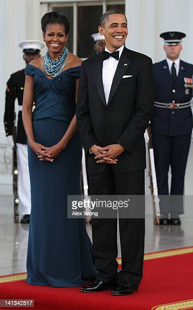 First lady Michelle and US President Barack Obama await the arrival of British Prime Minister David Cameron and his wife Samantha on the North...