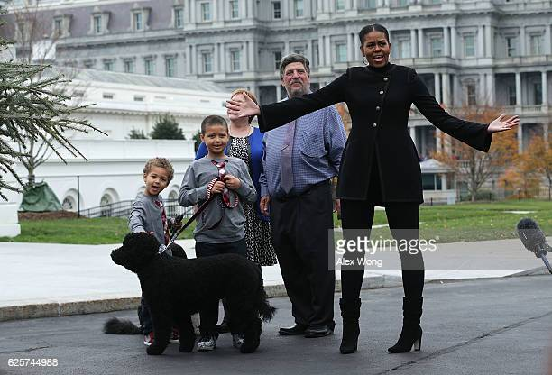 S first lady Michelle Obama accompanied by her nephews Austin and Aaron Robinson and her dogs Bo and Sunny is presented with the official White House...
