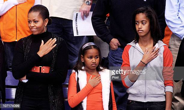 US first lady Michelle Obama and daughters Malia and Sasha stand for the National Anthem during a college basketball game at Howard University...