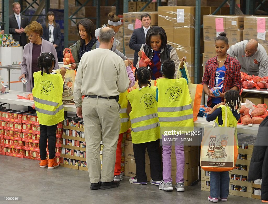 US First Lady Michelle Obama (2nd R) and daughters Sasha (R) and Malia (2nd L), along with her mother Marian Robinson, distribute food items at the Capitol Area Food Bank on November 21, 2012, a day ahead of Thanksgiving, in Washington, DC. AFP PHOTO/Mandel NGAN