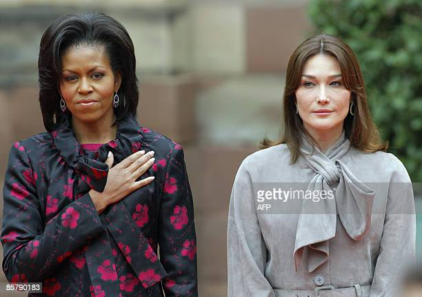US first lady Michelle Obama and France's first lady Carla BruniSarkozy listen to national anthems during a welcoming ceremony in Strasbourg on April...