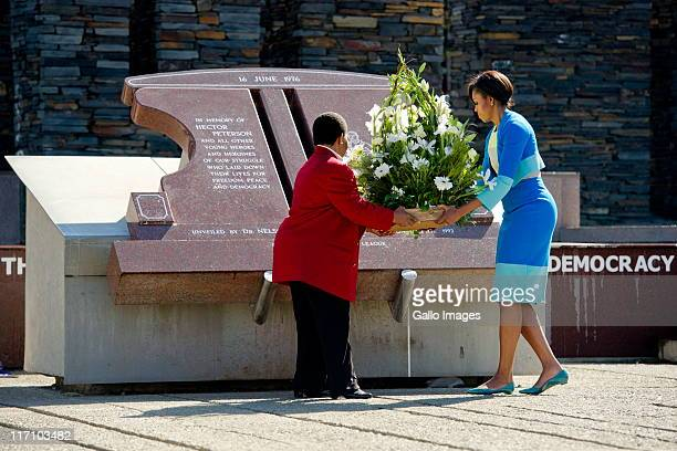 US First Lady Michelle Obama and Hector Pieterson's sister Antoinette Sithole place a bouquet of flowers at the Hector Pieterson memorial site on...