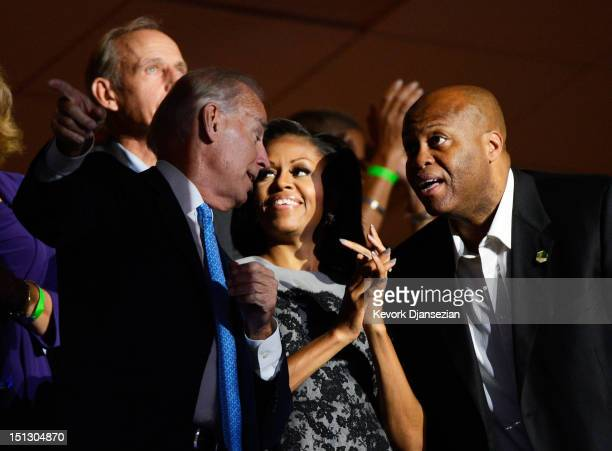 First lady Michelle Obama and her brother Craig Robinson talk with Democratic vice presidential candidate US Vice President Joe Biden in a box during...