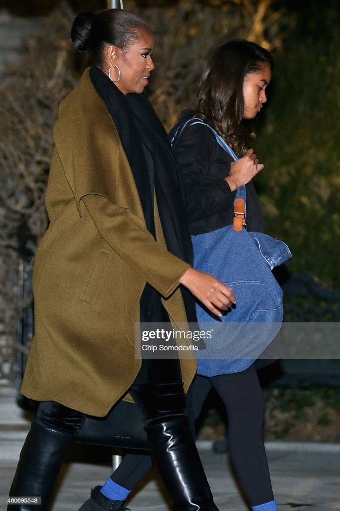 U.S. first lady Michelle Obama and her daughter Malia Obama leave the White House for their holiday vacation December 19, 2014 in Washington, DC. The first family will spend Christmas and the New Year in Hawaii.