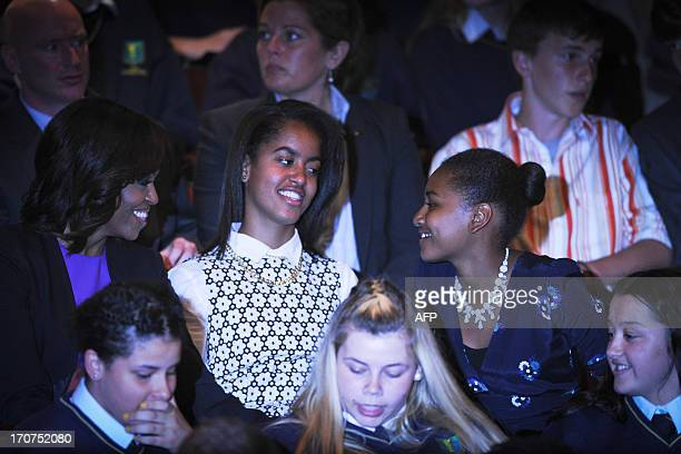 First Lady Michelle Obama and her two daughters, Sasha and Malia await the start of the Riverdance Performance in Dublin's Gaiety Theatre in Dublin,...