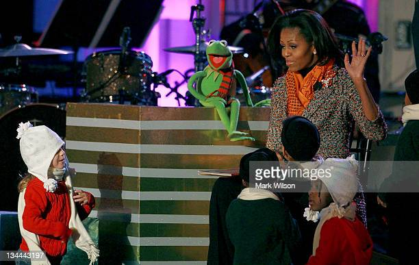 First lady Michelle Obama and Kermit the frog read a book to children during the National Christmas Tree lighting ceremony on December 1 2011 at the...