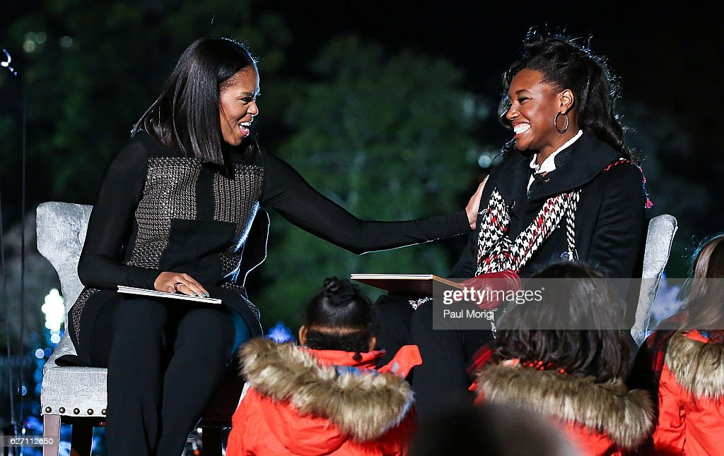 First Lady Michelle Obama (L) and Olympic medal winner Simone Manuel read 'Twas The Night Before Christmas' to children onstage during the 94th Annual National Christmas Tree Lighting Ceremony on the Ellipse in President's Park on December 1, 2016 in Washington, DC.