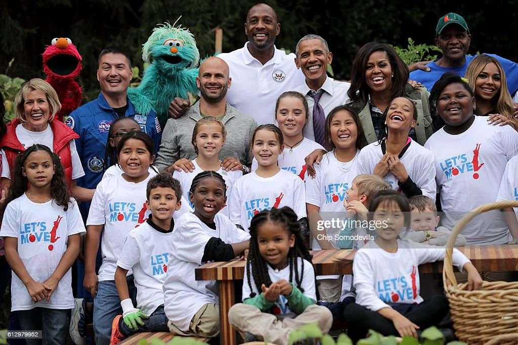 U.S. first lady Michelle Obama and President Barack Obama (C) pose for a group photograph during an event to harvest the White House Kitchen Garden on the South Lawn of the White House October 6, 2016 in Washington, DC. Guests included Sesame Street's Elmo and Rosita, NASA Astronaut Kjell Lindgren, NBC's Al Roker and Sam Kass, NBA All-Star Alonzo Mourning, Growing Power founder and CEO Will Allen, Produce Marketing Association President Cathy Burns and others. Students from across the country were invited to help pull vegetables and greens from the garden which was established by Michelle Obama in the spring of 2009. The garden is now a permanent feature on the White House grounds.