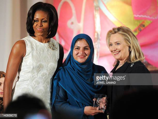 US First Lady Michelle Obama and Secretary of State Hillary Clinton pose with Shad Begum of Pakistan as she receives 2012 International Women of...