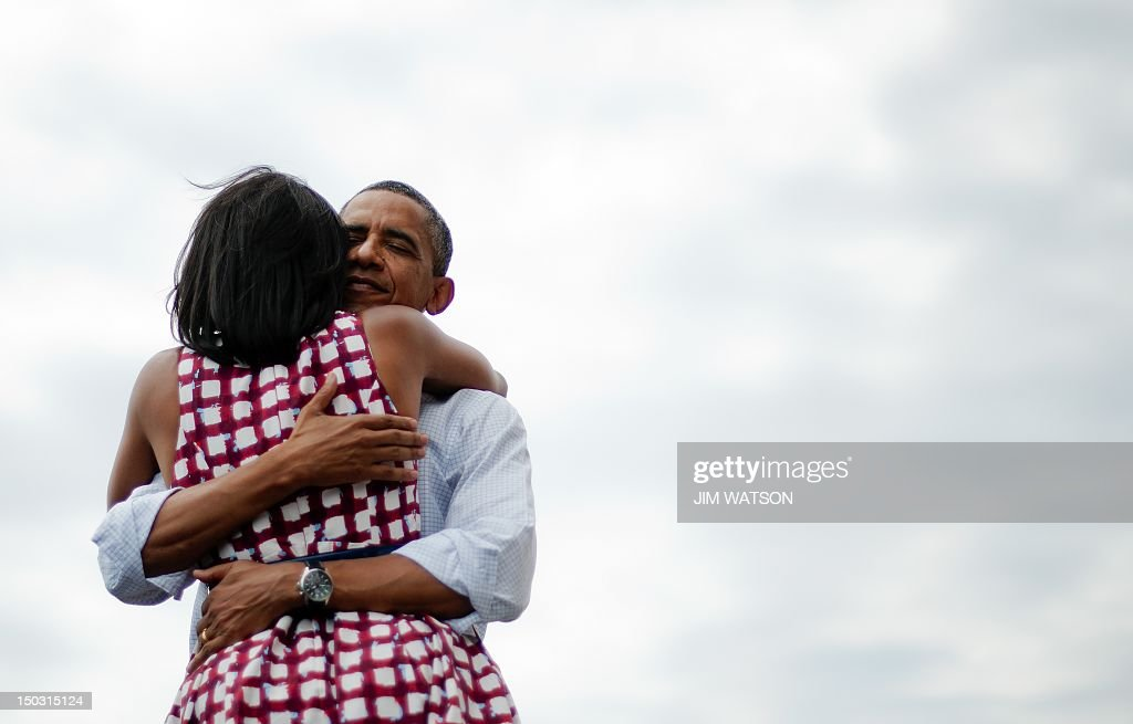 First Lady Michelle Obama (L) and US President Barack Obama (R) hug after delivering remarks during a campaign event at the Alliant Energy Amphitheater in Dubuque, Iowa, August 15, 2012, during his three-day campaign bus tour across the state. AFP PHOTO/Jim WATSON / AFP / JIM