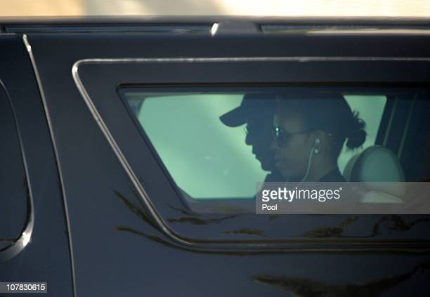First Lady Michelle Obama and US President Barack Obama ride in their SUV as they leave their Kailua residence on their way to Bobby Titcomb's beach...