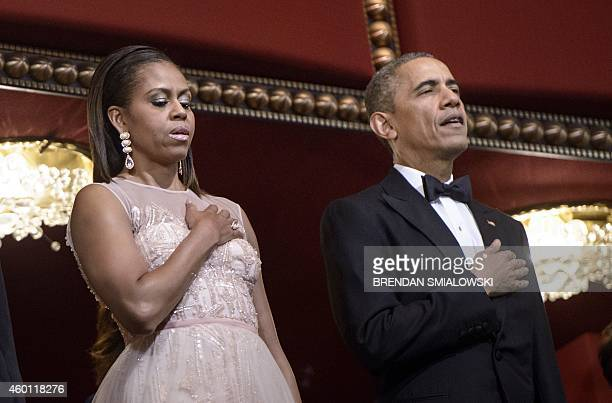 US first lady Michelle Obama and US President Barack Obama sing the US national anthem during the 37th Kennedy Center Honors at the Kennedy Center...