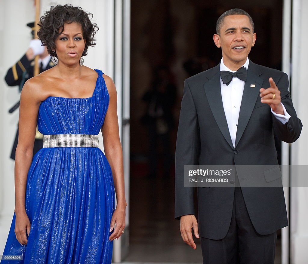 US First Lady Michelle Obama and US President Barack Obama wait on the red carpet for the arrival of the Mexican President and his wife May 19, 2010 on the North Portico at the State Dinner for Mexico at the White House in Washington, DC. AFP Photo/Paul J. Richards