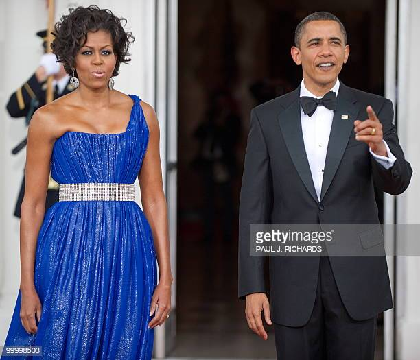 US First Lady Michelle Obama and US President Barack Obama wait on the red carpet for the arrival of the Mexican President and his wife May 19 2010...