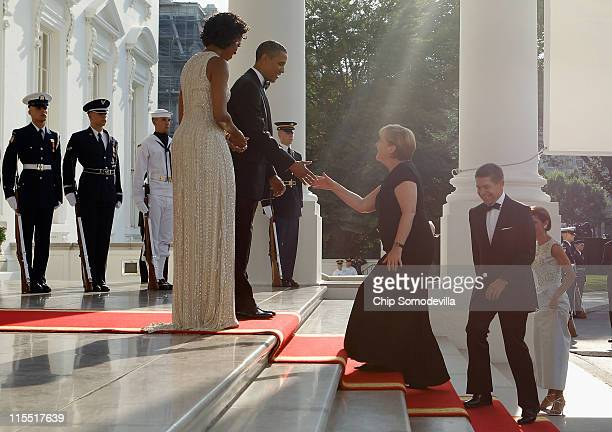 First lady Michelle Obama and US President Barack Obama welcome German Chancellor Angela Merkel and her husband Joachim Sauer on the North Portico of...