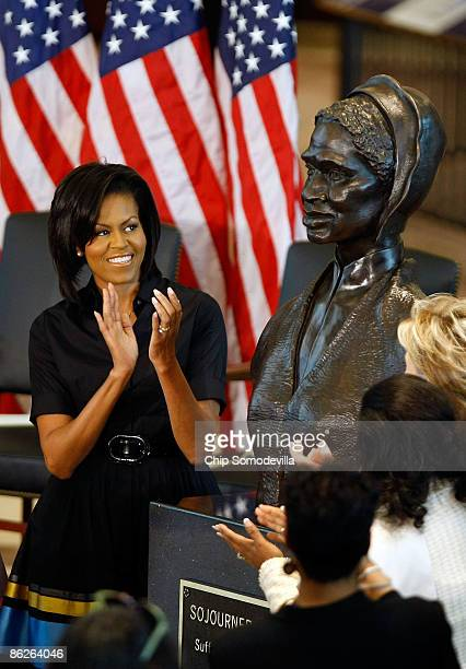 First lady Michelle Obama applauds the unveiling of the bust of Sojourner Truth in the US Capitol Visitors Center April 28 2009 in Washington DC...