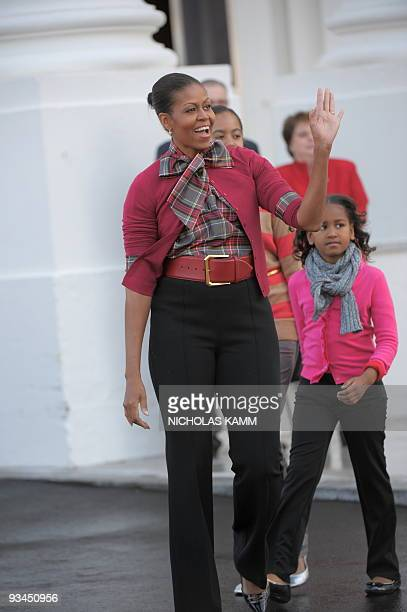 US First Lady Michelle Obama arrives with her daughters Sasha and Malia to receive the official White House Christmas Tree at the North Portico of...