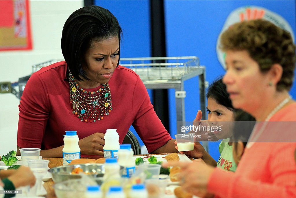 U.S. first lady Michelle Obama (L) convices Head Start student Wendy Zacarias (R) to drink milk during lunch as she visits New Hampshire Estates Elementary School May 19, 2010 in Silver Spring, Maryland. The school was awarded the USDA�s Healthier US School Challenge Silver Award in 2009 and partnered with a school in Mexico as part of the Monarch Butterfly Sister School Program. President of Mexico Felipe Calderon is on a state visit to Washington with the first lady of Mexico.