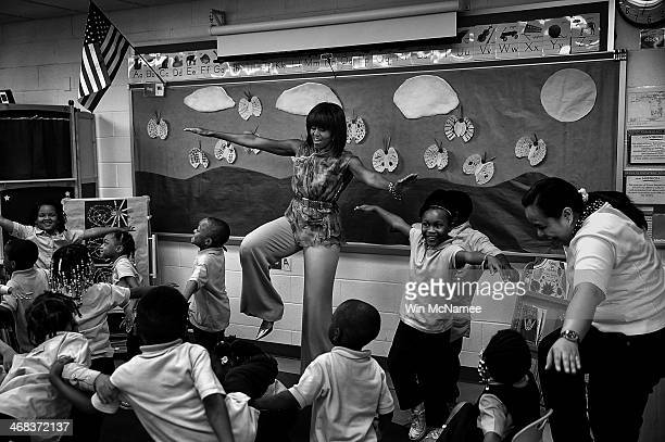 S first lady Michelle Obama dances with prekindergarten students while she visits the Savoy School May 24 2013 in Washington DC The Savoy School once...