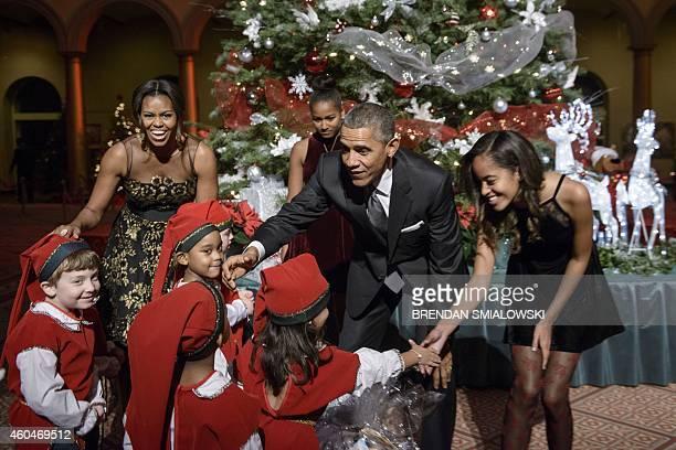 First Lady Michelle Obama , daughter Sasha Obama , US President Barack Obama and daughter Malia Obama greet children dressed as elves before the...