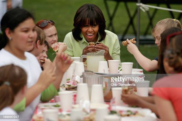 First lady Michelle Obama eats flat bread pizzas she and school children made with vegetables harvested from the White House Kitchen Garden at the...