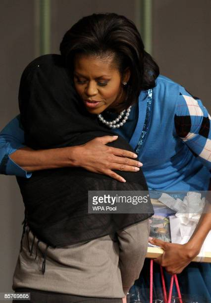 S first Lady Michelle Obama embraces a student during a visit to the Elizabeth Garrett Anderson Secondary School on April 2 2009 in Borough of...