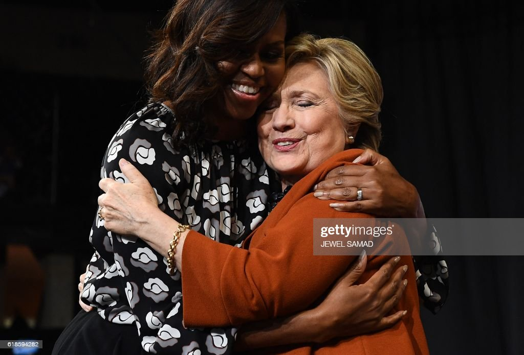 First Lady Michelle Obama embraces Democratic presidential nominee Hillary Clinton during a campaign rally in Winston-Salem, North Carolina on October 27, 2016. Michelle Obama, surprise star of the 2016 White House campaign, hit the trail Thursday with Democrat Hillary Clinton as the former and current first ladies fight to conquer battleground states before Election Day. / AFP PHOTO / Jewel SAMAD