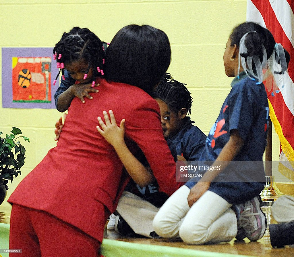 US First Lady Michelle Obama embraces students at the River Terrace school after an event highlighting physical activity as a critical element of the 'Let's Move' initiative on April 21, 2010 in the North East section of Washington, DC. AFP PHOTO / Tim Sloan