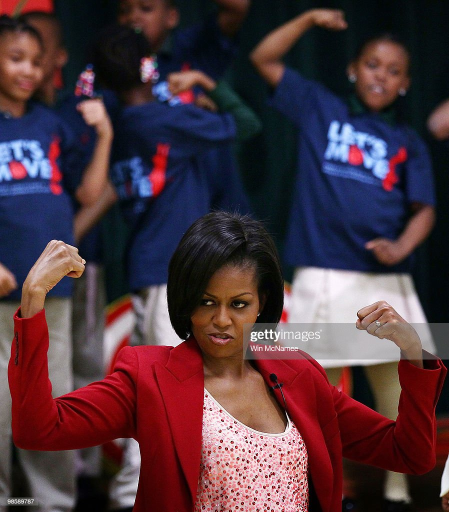 U.S. first lady Michelle Obama flexes her muscles as she exercises with schoolchildren at the River Terrace School April 21, 2010 in Washington, DC. Mrs. Obama visited the school to highlight physical activity as a critical element of the 'Let�s Move!' initiative with several Olympians and Paralympians, including 2010 Olympians Shani Davis and Hannah Kearney and 2010 Paralympians Alana Nichols and Heath Calhoun.